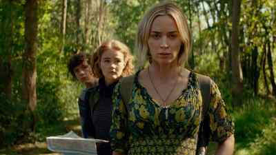 Noah Jupe, Millicent Simmonds, and Emily Blunt walking in the woods in A Quiet Place Part II.
