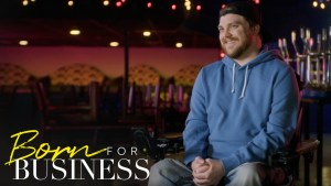 Chris in a concert venue speaking to camera in a scene from Born For Business. Show logo in bottom left