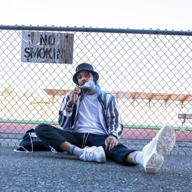 """Man sitting on pavement smoking Delta-8-THC. There is a fence behind him with a sign that says """"No smoking."""""""