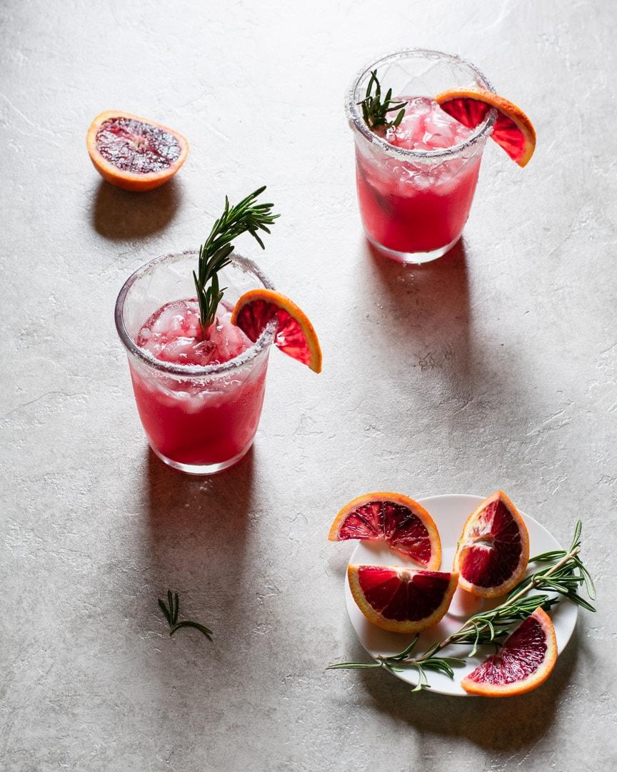 2 blood orange margaritas with sliced blood oranges and rosemary
