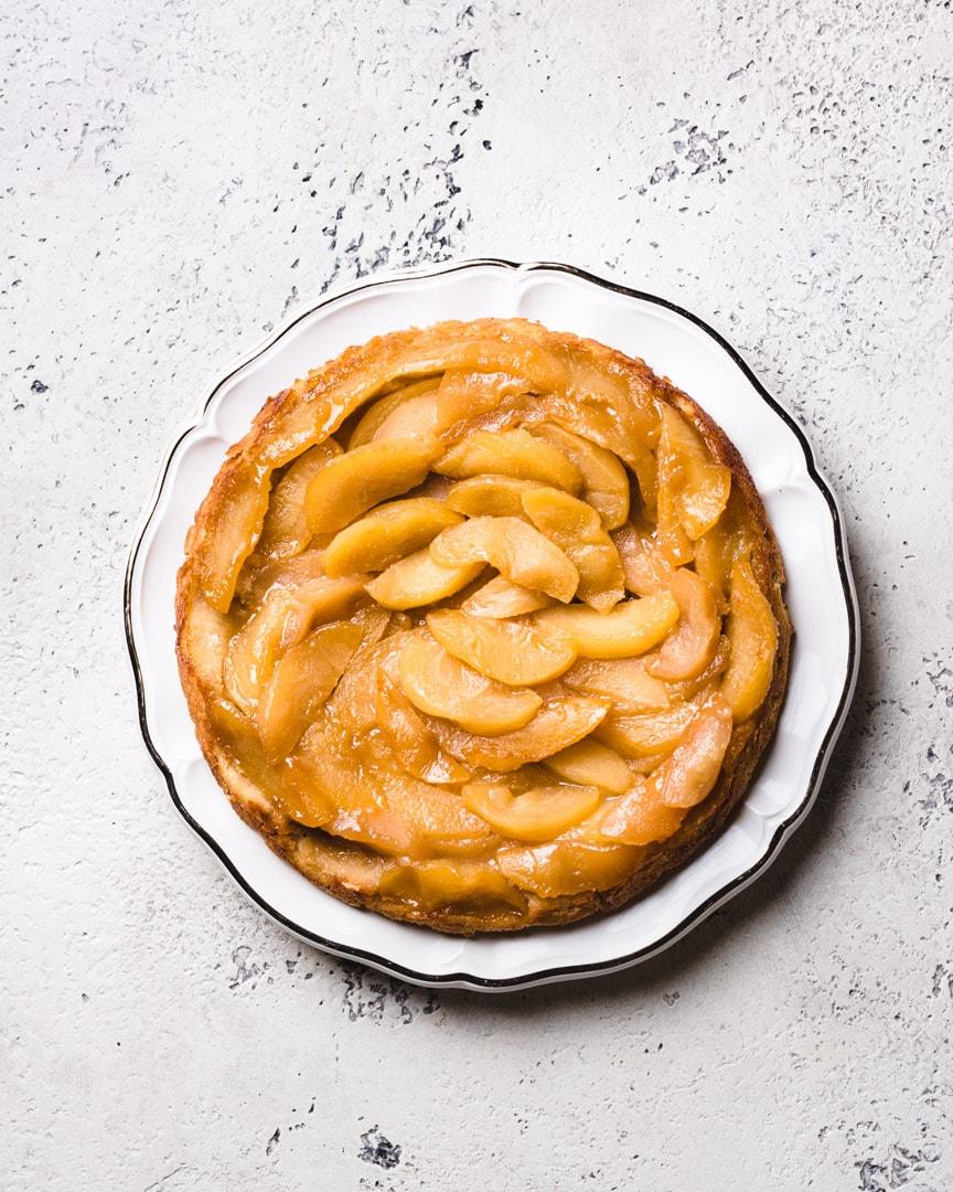 vegan apple tart tatin on white plate and textured background