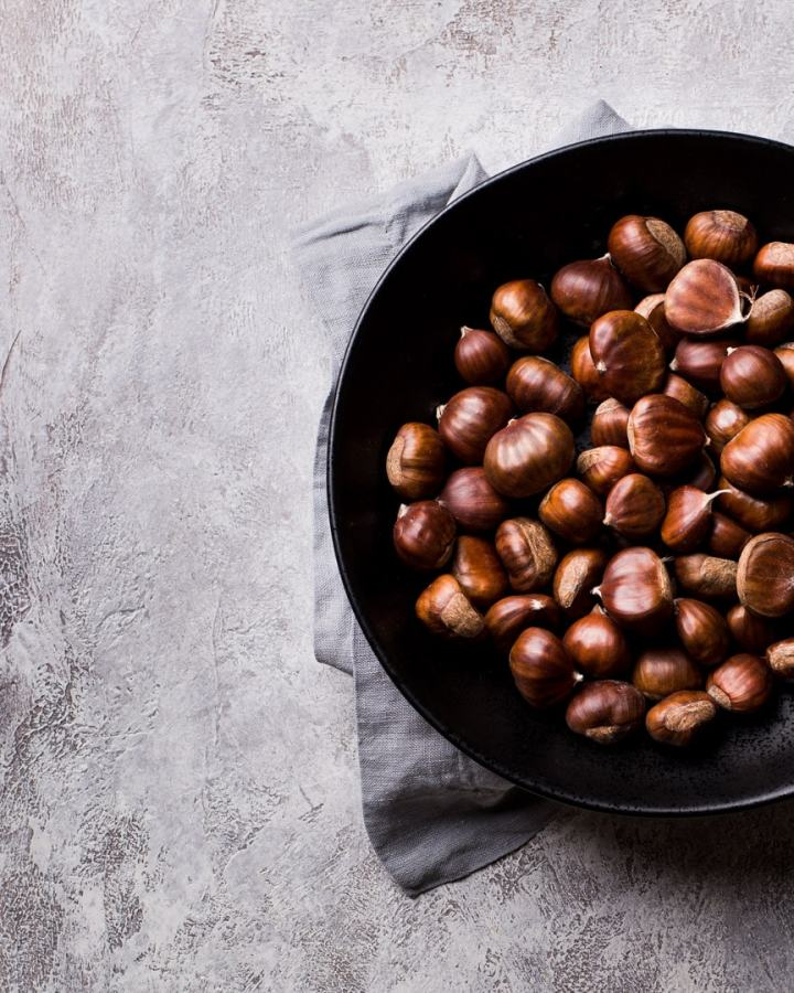 raw chestnuts in black bowl on grey napkin