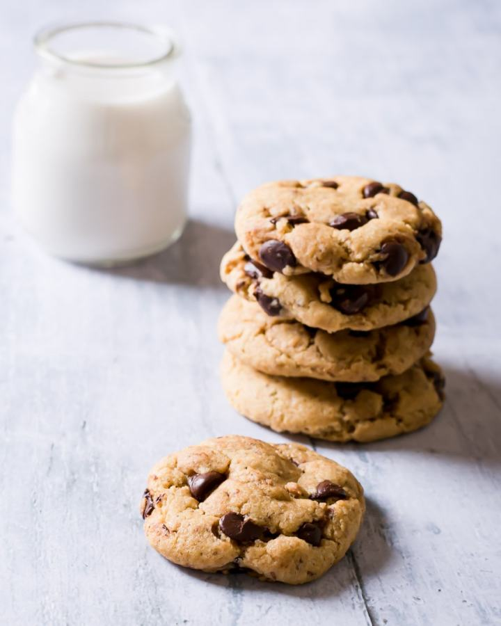stack of chocolate chip cookies with small container of almond milk