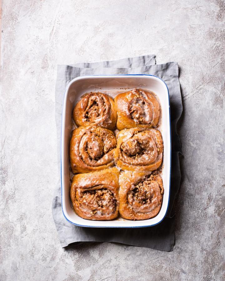 six pumpkin sweet potato cinnamon rols in a baking dish on a grey napkin