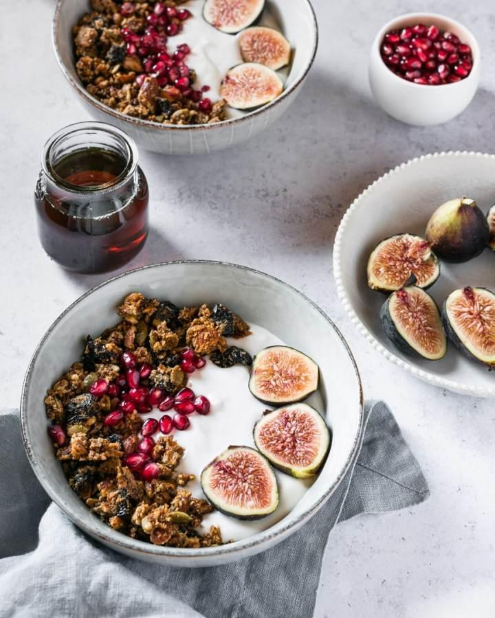 granola and cashew yogurt bowl with figs, maple syrup, pomegranate