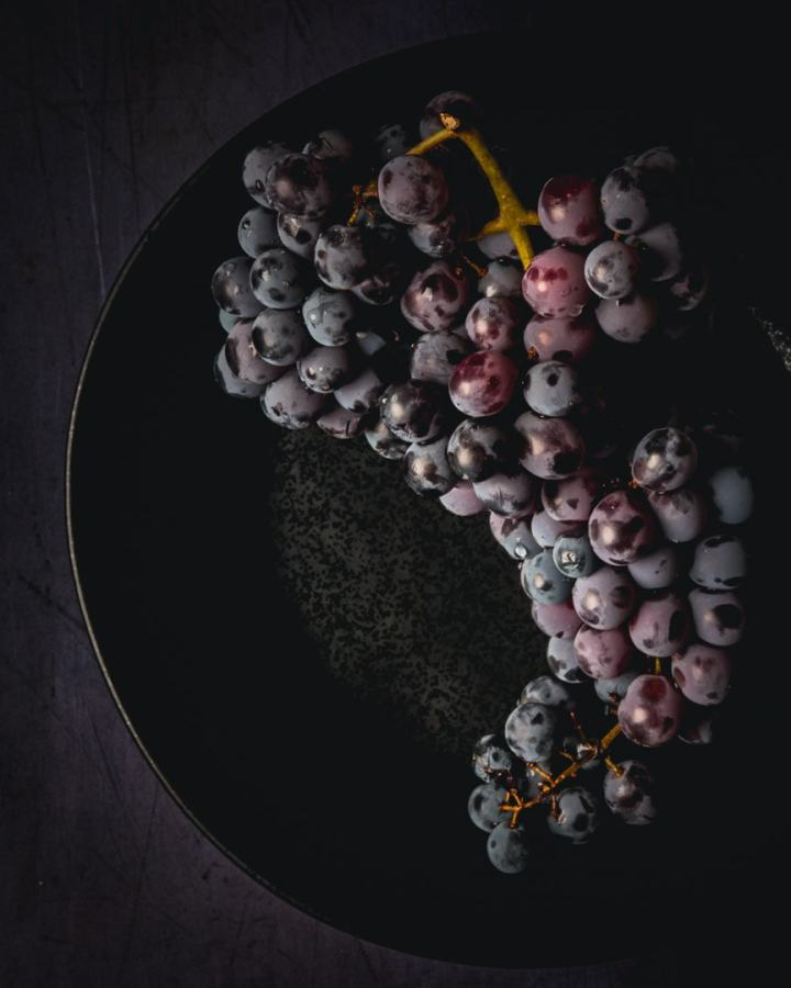 Thomcord grapes on a black plate on a dark background
