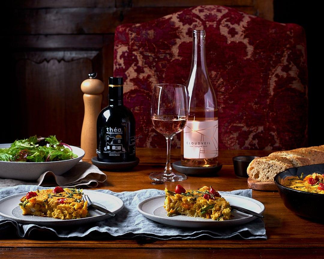 table setting with vegan frittata, green salad, bread, and wine