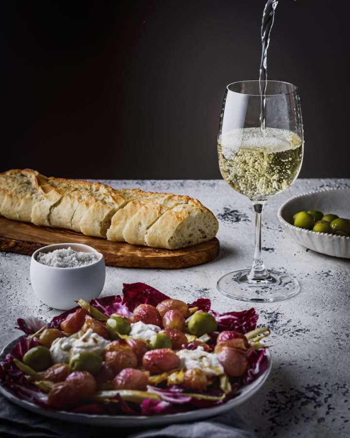 pouring a glass of wine on table with salad and bread