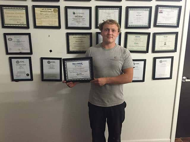Zac holding his IICRC WRT certification 480