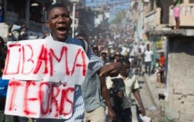 "A protester carries a sign that reads in Creole ""Obama terrorist"" during a protest against President Michel Martelly's government to demand the cancellation of this week's elections, in Port-au-Prince, Haiti, January 19, 2016. (AP Photo /  Dieu Nalio Chery"