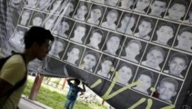 A child stands underneath a banner showing the photographs of the 43 missing students of the Ayotzinapa teachers' training college. | Photo: Reuters