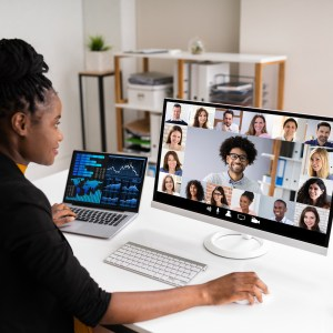 A woman sits in front of a desktop computer. She has one hand on the mouse. Over her shoulder, we can see that her screen has the image of many faces on it, as though in a web conference. She also has a small laptop on the side of the dek.