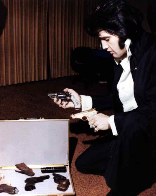 ELVIS PRESLEY examines a collection of guns