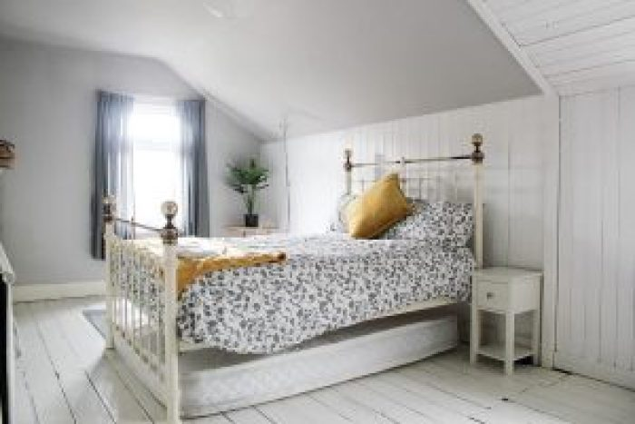 A typical bedroom features light, neutral colors and sturdy hardwood floors