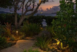 The lighting scheme highlights the courtyard landscaping and illuminates the pathways, boulders, and rocky areas that lead to the beach.