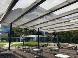 The draped metal mesh canopy provides shading while offering connectivity to a redesigned amenities building and indoor eating space.