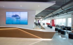 A long, sleek reception desk was inspired by the forms of cruise ships and custom-built for Virgin Voyages by the design team at IA Interior Architects.