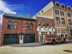 The Market Street Firehouse receives an exterior upgrade, including Haas garage doors in dark green, matching trim work in dark green and a red entry door.