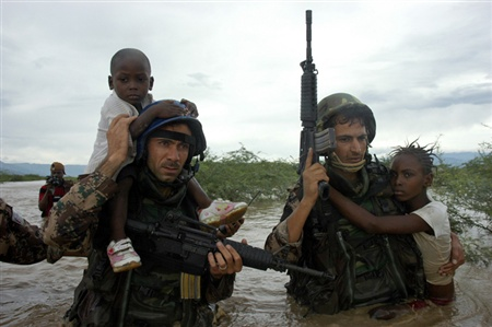 U.N. peacekeepers help Haitian children cross a river after floods near Port-au-Prince September 7, 2008. Officials said at least 61 people had died in floods in impoverished Haiti on top of 500 killed last week by Tropical Storm Hanna.