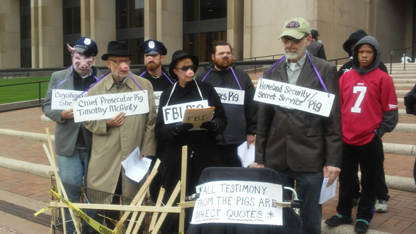 Revcoms dressed as pigs stand on the steps of the Justice Center in downtown Cleveland.