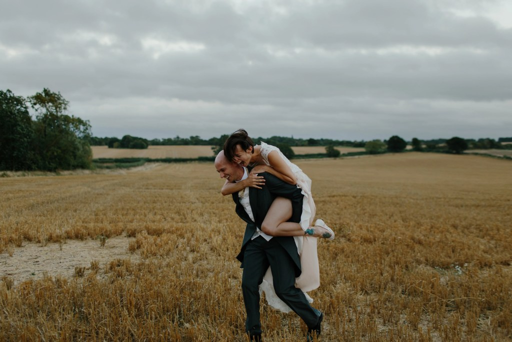 bride rides groom piggy back through farm field