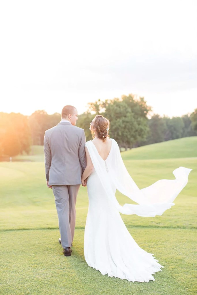 elegant bride with cape walks into horizon with groom