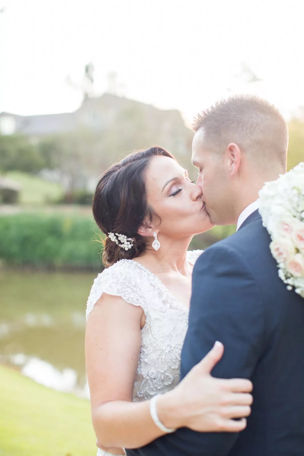 brunette bride kisses her groom in bright and airy outdoor space
