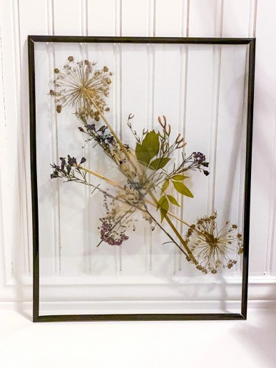 custom etching is nested by pressed florals in a floating frame
