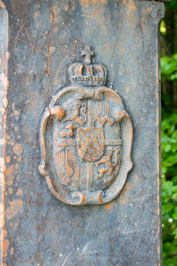 A Bavarian crest stands on a stone post at the Königssee.