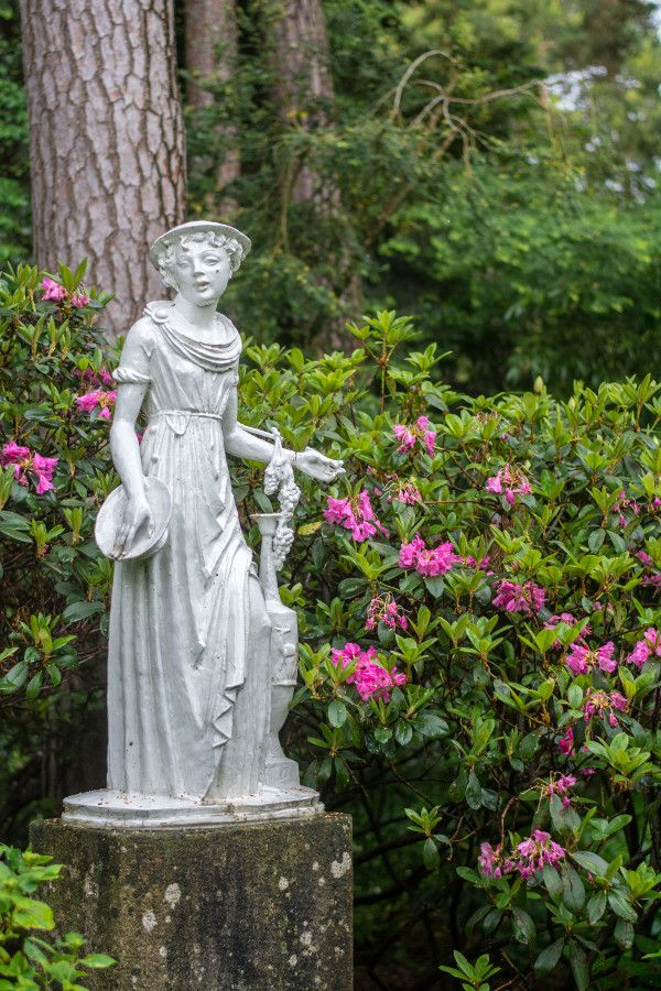 A statue of a lady surrounded by rhododendrons at the Munich Botanical Garden.