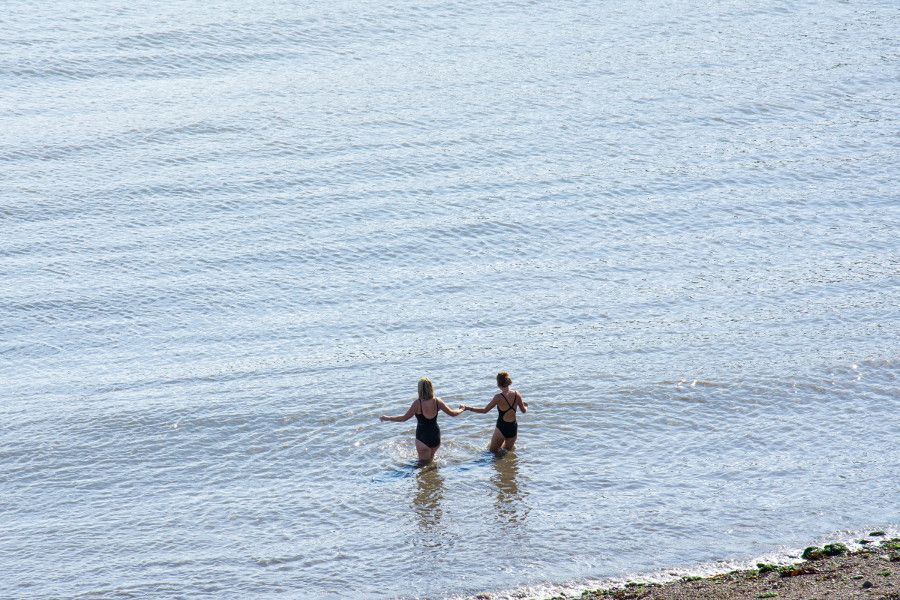 Two swimmers carefully wade into Balscadden Bay in Howth, Ireland.