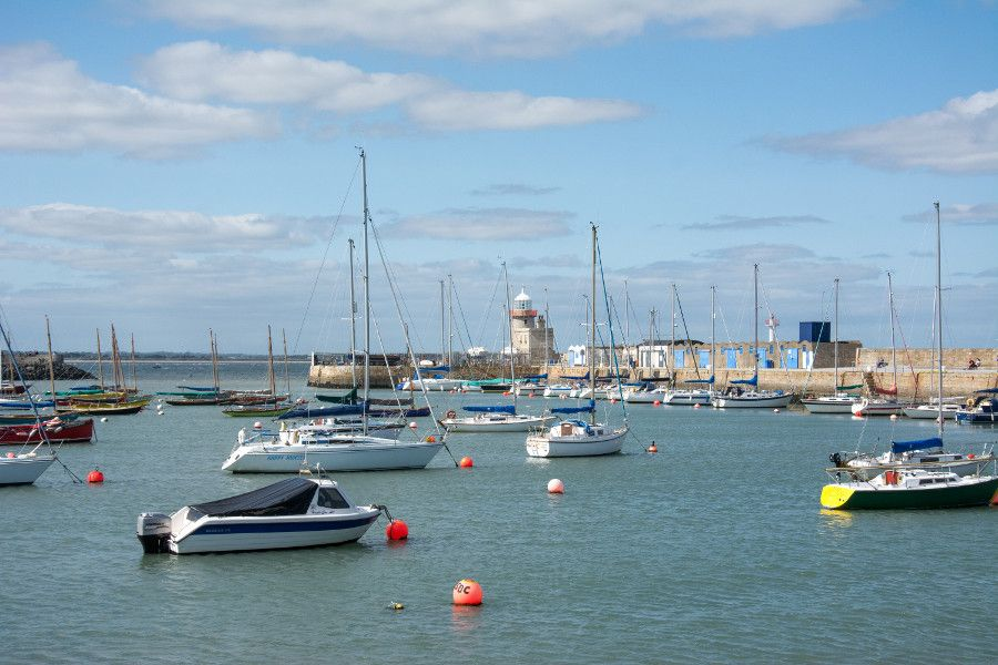 Boats in the harbor in front of the Howth Lighthouse.