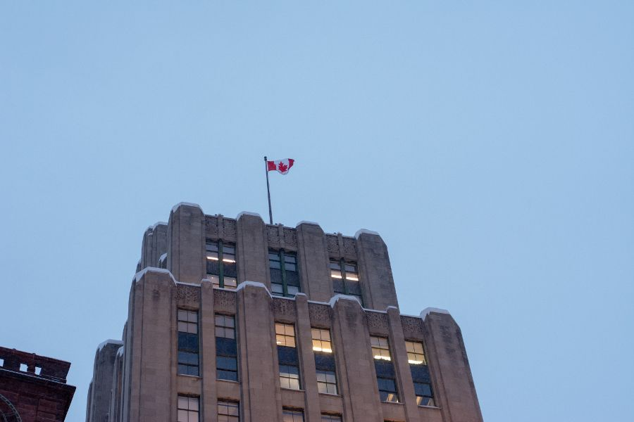 The Canadian flag sits atop an Art Deco building at Place D'Armes in Montreal.