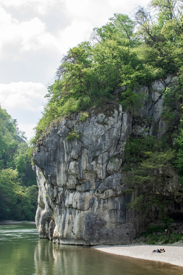 Sunbathers lie on the stone beach near the white stone along the Danube River Gorge, or Donaudurchbruch.
