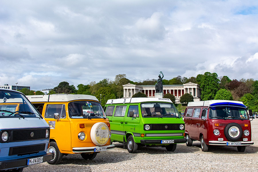 Four colorful VW Westfalia vans stand before the Bavaria statue on the Wiesn for the ACM Oldtimer-Treffen.