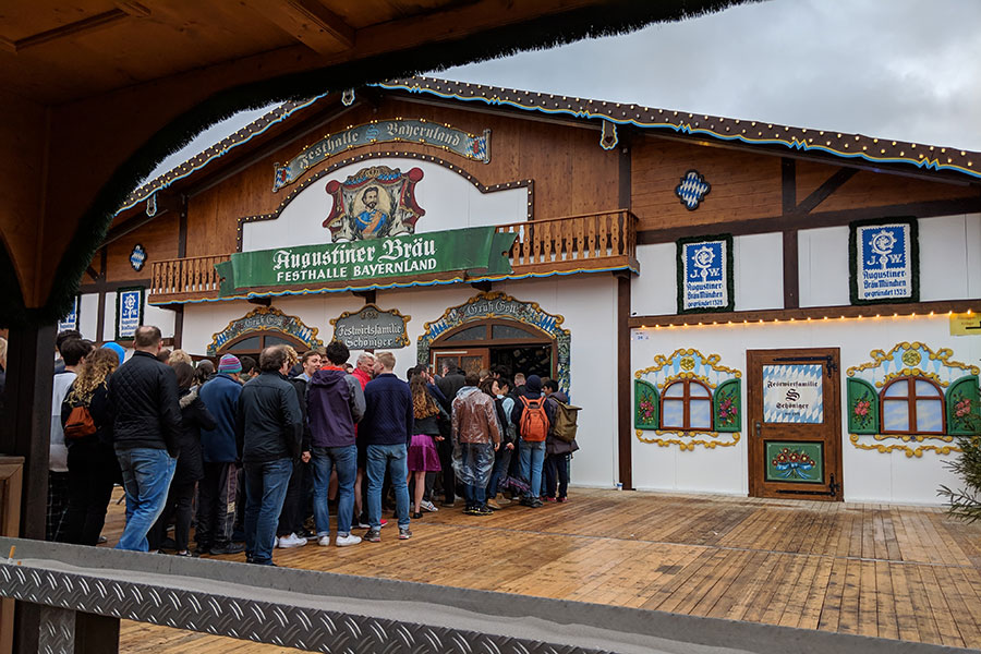 A line of people queue up in front of the Festhalle Bayernland for Frühlingsfest.