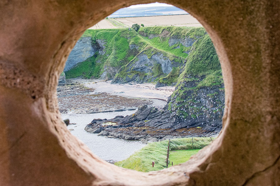 Looking through the stone at Tantallon Castle, birds fly along the cliffs.