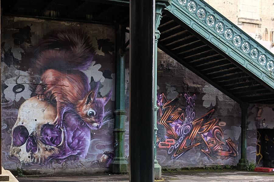 Squirrel on a skull street art in Glasgow, Scotland.
