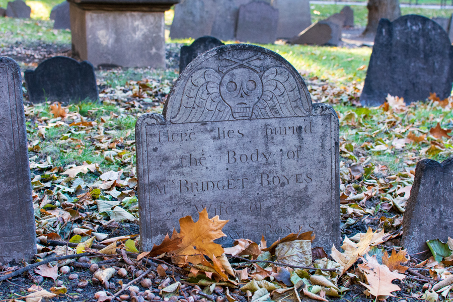 A stone headstone among the leaves at Granary Burying Ground in Boston.