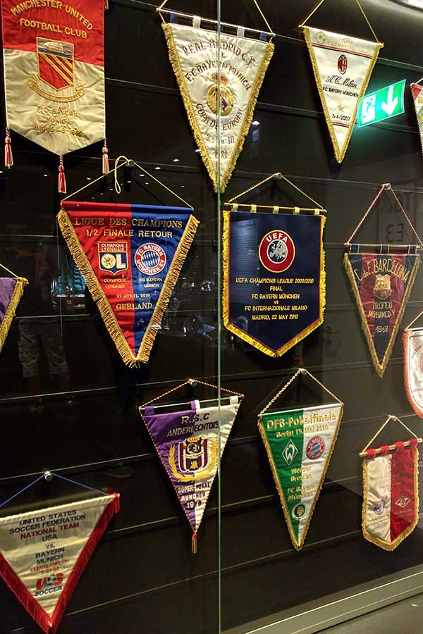 Flags line a wall inside the FC Bayern Erlebniswelt Museum.