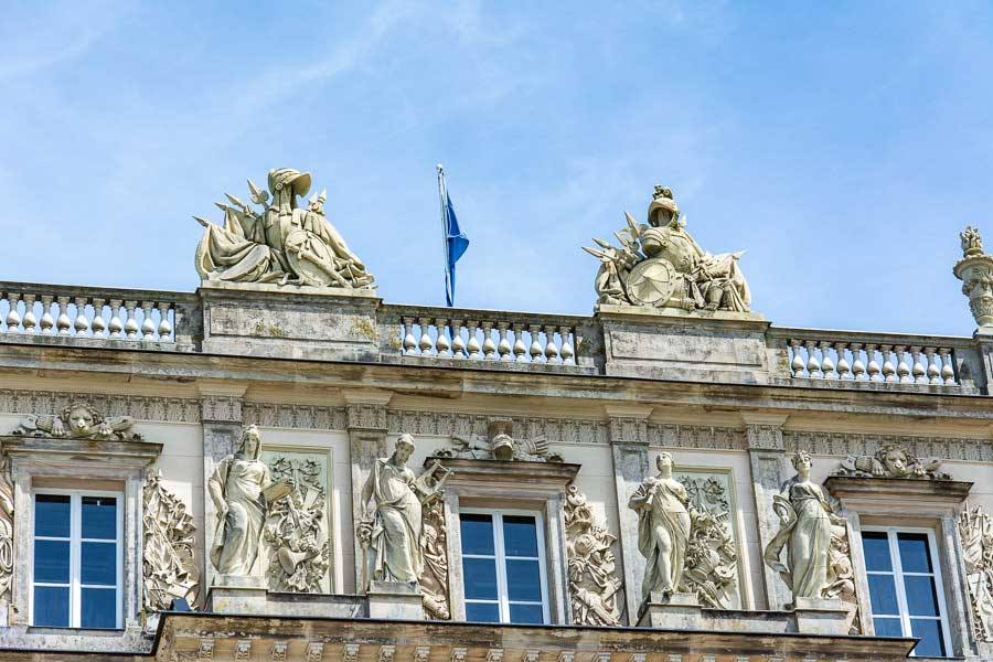 Elaborate stone sculptures line the top of the Herrenchiemsee New Palace.