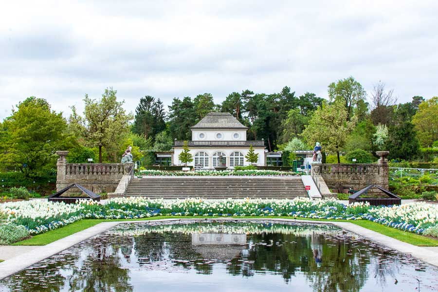 The Schmuckhof sits before a reflecting pool at the Munich Botanical Garden.