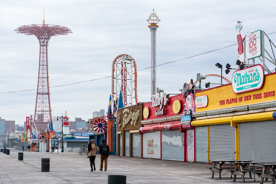 A couple walk the boardwalk during winter at Coney Island.