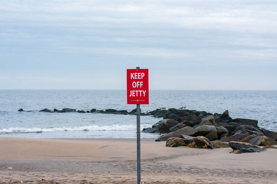 "A sign says ""keep off jetty"" along the Coney Island beach."