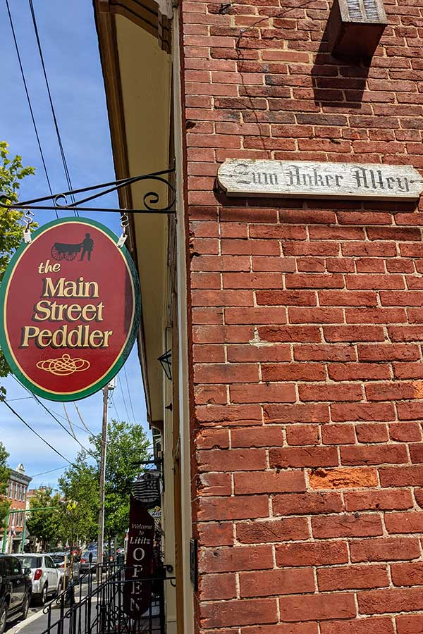 Signs for the Main Street Peddler and Zum Anker Alley line Main Street in Lititz, PA. Shopping will top the list of things to do in Lititz, PA.
