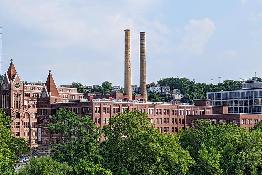 Two chimneys soar to the sky from the one time HJ Heinz Company complex of brick buildings.