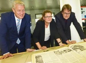 Über historische Presseerzeugnisse gebeugt: Astrid Blome, künftige Leiterin des Instituts für Zeitungsforschung, flankiert von Kulturdezernent Jörg Stüdemann (li.) und Bibliotheksdirektor Johannes Borbach-Jaene. (Foto: Bernd Berke)