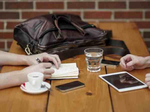 Imagem de um close na mesa de uma reunião casual e um tablet à mostra