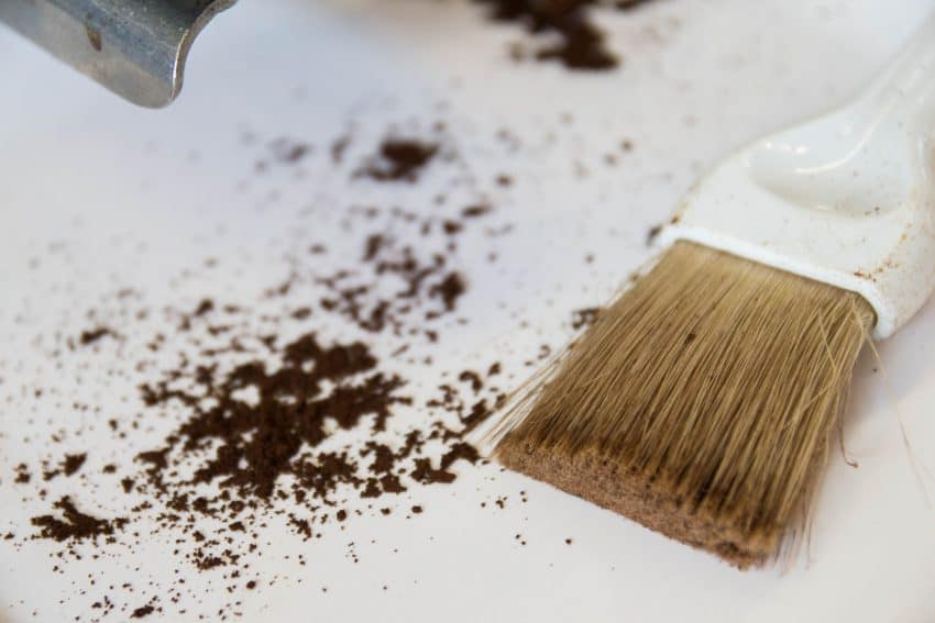 Image shows remnants of coffee powder on a table next to a cleaning brush.