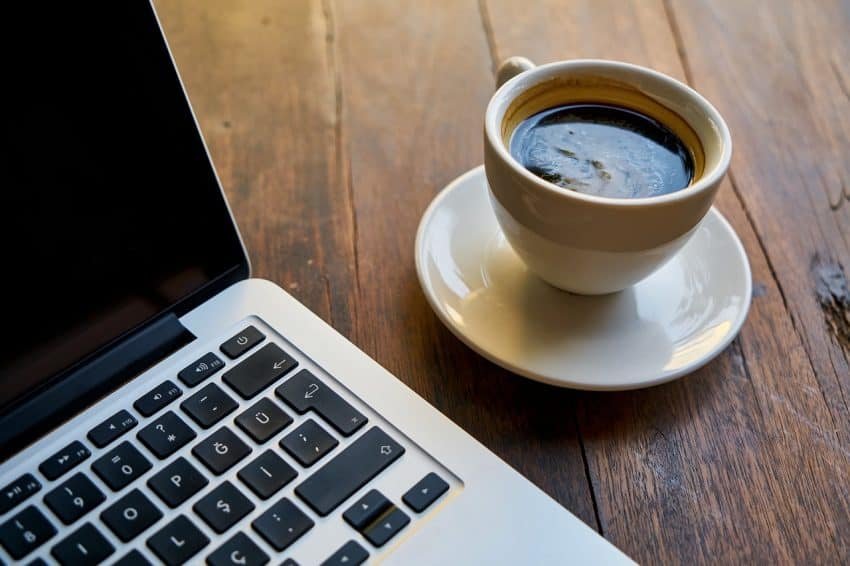 Image shows cup of espresso next to computer.